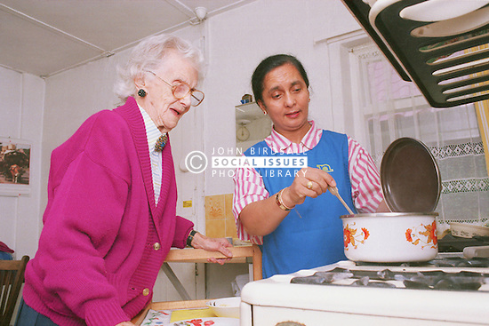 Carer wearing uniform assisting elderly woman to cook meal in kitchen,