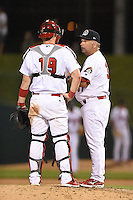 Peoria Chiefs manager Joe Kruzel (37) talks with catcher Carson Kelly (19) during a pitching change during a game against the Kane County Cougars on June 2, 2014 at Dozer Park in Peoria, Illinois.  Peoria defeated Kane County 5-3.  (Mike Janes/Four Seam Images)