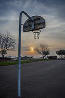 At a neighborhood park, a rusting basketball backboard stands over an asphalt court, its hoop and chainlink net against a cloud streaked winter sky near sunset.