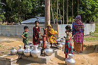 Bangladesh, Teknaf, Cox's Bazar. Leda Rohingya Refugee Camp. The Rohingya, a Muslim ethnic group  denied citizenship in Burma/Myanmar have escaped persecution from Burmese militants in their country. There are up to 500,000 refugees and migrants living in makeshift camps in Teknaf, Cox's Bazar. Girls collecting water at the pump.