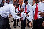 """Antioch High School hosted """"United We Fulfill The Dream"""" celebration for Martin Luther King day on Monday, January 19, 2015 in Antioch, California.  Sean Barksdale of GRIOT helps the young men of the group tie their ties before the celebration.  Photo/Victoria Sheridan"""