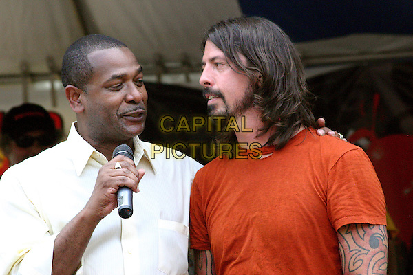 """DOUG FRANKLIN (Safety-Service Director) & DAVE GROHL (Foo Fighters, Nirvana).Dave Grohl is presented with a key to the city and a street, Dave Grohl Alley, dedicated to him. Born in Warren, Ohio, Grohl, frontman for the Foo Fighters and drummer for grunge rock band Nirvana, arrived at Courthouse Square about 3pm for the culmination of the weeklong """"Music Is Art"""" Festival during the dedication of a downtown alley in Dave Grohl's name. .Warren, Ohio, USA, 1st August 2009..half length orange t-shirt microphone beard facial hair                            .CAP/ADM/JD.©Josh Drespling/Admedia/Capital Pictures"""