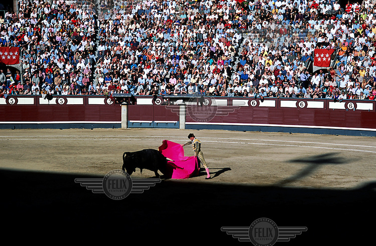 A packed crowd watch as a matador uses his cape to fend off a bull during a bullfight at the Plaza de Toros de las Ventas bullring in Madrid's Salamanca district..