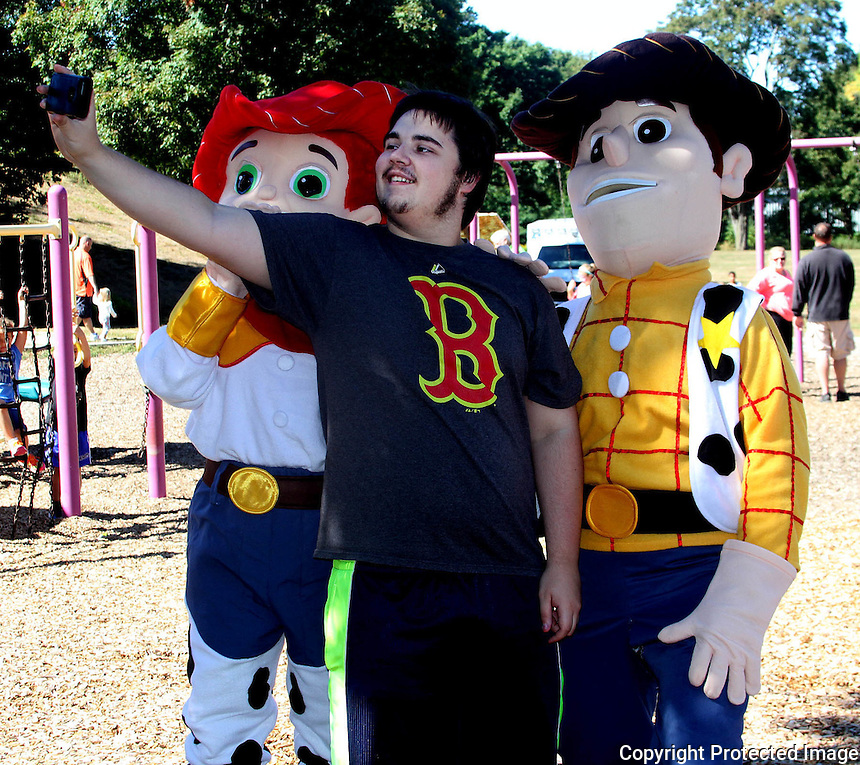 James Hebert takes a photo with Woody and Jessie at the Sacred Heart Church of Weymouth and the St. Thomas Moore Church of Braintree family Picnic, Sunday September 14, 2014 at the Weston Park in Weymouth.(Photo by Gary Wilcox)