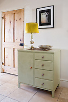 In the kitchen a vintage cabinet has been painted a subtle shade of palest green, offset by the lemon-yellow shade of the table lamp on top