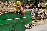 A young Palestinian boy looks on as a youth using a T-shirt to hide his face manoeuvres rubbish bins to form a crude barricade to impede the movement of Israeli army jeeps in anticipation of a clash following the suppression of a non-violent demonstration against Israel's controversial separation barrier by Israeli soldiers in the West Bank town of Beit Jala, near Bethlehem on 11/07/2010. Ultimately no clash occurred at this location, instead a brief skirmish ensued on the opposite side of the valley.
