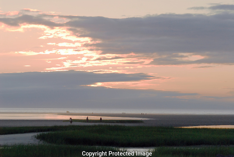 Beach combers walk the sand flats at Paine's Creek, Brewster, Massachusetts, on a hazy summer evening.