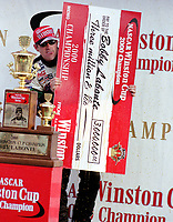 Bobby Labonte peeks from behind his check as his pit crew tries to spray him with Coca Cola as they celebrate Labonte's 2000 Winston Cup Championship at Homestead, Florida in November 2000.(Photo by Brian Cleary)