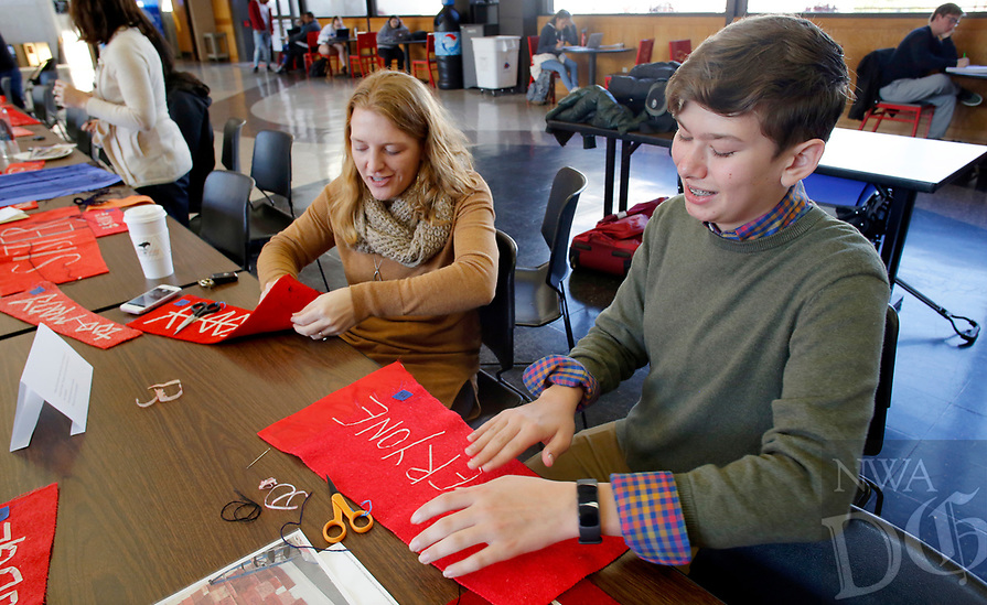 NWA Democrat-Gazette/DAVID GOTTSCHALK Cooper Tidwell (right), and eighth grade student at Farmington Junior High, sews Wednesday, November 7, 2018, with Donna Jones, director of recruitment and outreach at The School of Art at the University of Arkansas, in a sewing circle hosted by artist Marie Watt in the Arkansas Union on the campus in Fayetteville. Watt, who is featured in the Crystal Bridges' exhibition Art for a New Understanding: Native Voices, 1950s to Now, was working on a collaborative assemblage of sewing panels featuring lyrics from the Marvin Gaye song What's Going On released in 1971. Tidwell was participating in a career exploration program that had him shadow Jones.