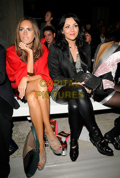 GUEST & MARTINE McCUTCHEON.The Pam Hogg Show, London Fashion Week, Day Two, Somerset House, The Strand, London, England..September 19th, 2009.LFW full length black pvc leather leggings sitting red shawl cape jacket profile .CAP/CAN.©Can Nguyen/Capital Pictures.
