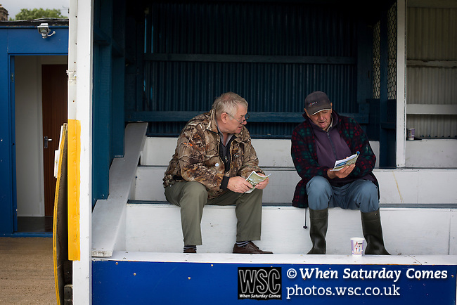 Clitheroe 0 Consett 1, 20/08/2016. Shawbridge, Northern Premier League Division One North. Two home supporters compare programme notes inside the ground before Clitheroe played Consett at Shawbridge in an FA Cup preliminary round tie. Northern Premier League division one north team Clitheroe were formed in 1877 and have played at the same ground since 1925. Visitors Consett, from the Northern League division one, won the match 1-0, watched by 207 spectators. Photo by Colin McPherson.