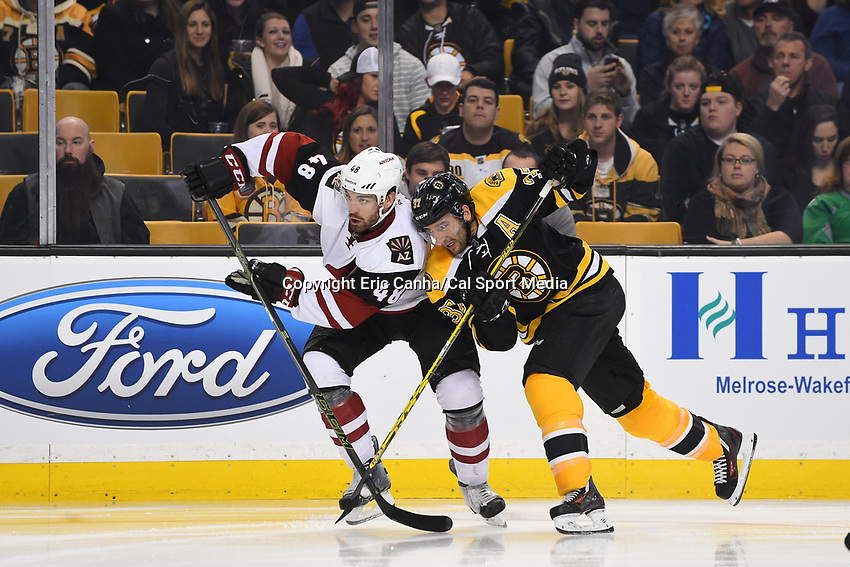 Tuesday, October 27, 2015: Arizona Coyotes left wing Jordan Martinook (48) and Boston Bruins center Patrice Bergeron (37) battle to get to the puck during the National Hockey League game between the Arizona Coyotes and the Boston Bruins held at TD Garden, in Boston, Massachusetts. The Coyotes lose to the Bruins 6-0 in regulation time. Eric Canha/CSM