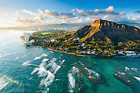 An aerial view of O'ahu's Diamond Head at sunset, with waves heading towards the edge of the Gold Coast.