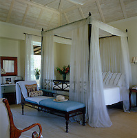 A four-poster guest bedroom has delicate voile bed-hangings and a mahogany daybed on a rope-sisal rug