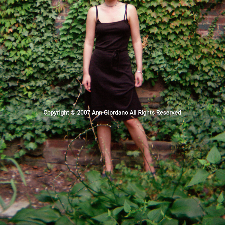 Woman from neck down in black sundress standing in garden with ivy on brick building in background and Hostas plants in foreground