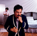 middle-aged man in bathrobe coughing, wife in background offers water