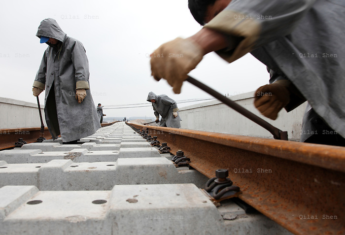 Workers lay railway tracks near the new railway station in Shanghai, China on 01 March 2010. In just a few years, China has built the world's longest high-speed rail network, named China Rail High-speed (CRH), and continues to expand despite accusations of technology pilfering and safety concerns. On July 23rd, 2011, two high-speed trains in eastern China collided due to supposed malfunctioning in the signaling system, killing 40 and injuring hundreds, meanwhile a slew of corruption scandals at China's rail ministry has surfaced recently.