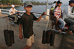 CAMBODIA  -  APRIL 3, 2005:  A young boy carries bamboo containers filled with sugar palm sap over a bridge across the Kampot River as moped riders pass him in the background on April, 3, 2005  in Kampot, Cambodia.  (PHOTOGRAPH BY MICHAEL NAGLE)