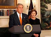 United States President George W. Bush announces he will widen economic sanctions on Myanmar's military rulers, piling on pressure for a transition to democracy after a bloody crackdown on anti-junta protests, in the Diplomatic Room of the White House in Washington, DC on October 19, 2007. The move comes only days after the European Union increased its sanctions against the regime. Standing with the President is first lady Laura Bush, right.<br /> Credit: Aude Guerrucci / Pool via CNP