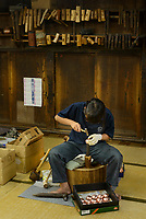 "A ""tsuiki"" copperware artisan at work. Gyokusendo, Tsubame, Niigata Pref, Japan, August 24, 2017. Traditional copper metalworking company Gyokusendo was founded in 1816 and is a registered as a traditional craft of Japan. At Gyokusendo, in a highly-skilled craft process, complex items such as teapots are beaten from a single sheet of copper using hammers and hundreds of other specialist tools."