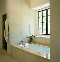 The bathroom is tiled floor-to-ceiling with large natural-coloured marble tiles