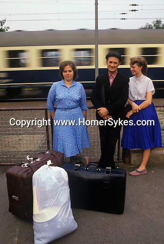 Friedland refugee camp West Germany. 1980's. Soviet-Germans return as refuges from the Soviet Union to freedom in the west.  Having been processed, documents checked etc, this family wait at the train station with their belongings for a train to take them to a new2 life.