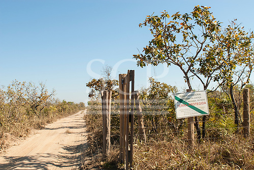 "Mato Grosso State, Brazil. Entrance to the Indigenous Park of the Xingu with FUNAI sign ""Protected Land, no access for strangers""."