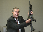 Charles Colman,  Bureau of Alcohol, Tocacco, and Firearms (ATF) fingerprint expert, holds the Bushmaster rifle used in the sniper shootings as he gestures during his testimony in the trial of sniper suspect John Allen Muhammad, in courtroom 10 at the Virginia Beach Circuit Court in Virginia Beach, Virginia on November 5, 2003.<br /> Credit: Dave Ellis - Pool via CNP