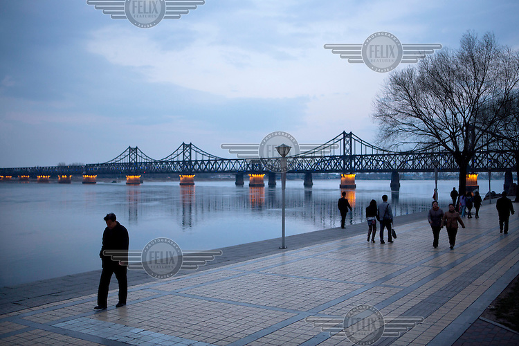 People walk along a prominade beside the Yalu River. In the background is the Sino-Korean Friendship Bridge. It was originally built by the occupying Japanese between 1937 and 1943 and links the North Korean city of Sinuiju, on the far side, with the Chinese city of Dandong. /Felix Features