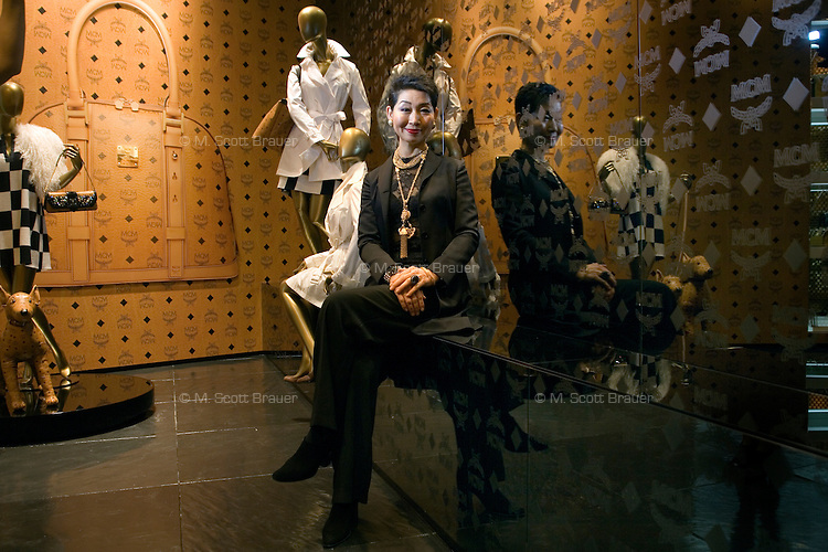 Portrait of Mrs. Sung-Joo Kim among mannequins displaying items from the MCM Signature Cognac Visetos line at the new MCM Shanghai flagship store on the Bund in Shanghai, China, on Tues., Jan. 26, 2010.  A glamorous fashion line in the 1980s, South Korean billionaire Sung-Joo Kim has purchased the MCM luxury brand in hopes of reinvigorating the brand.  Now Sung-Joo Kim is trying to replicate the brand's Asian success in Western markets, part of a greater shift of Asian luxury brands being exported to American and European high streets.  The MCM Shanghai flagship store, located on the world-famous Bund in Shanghai, was opened on Tues., Jan. 26, 2010...CREDIT: M. Scott Brauer for the Wall Street Journal
