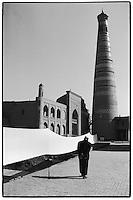 Uzbekistan - Khiva - Old man passing by the Islam Khodja minaret