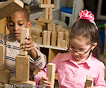 Education preschool 4 year olds block area boy and girl building large structure together out of wooden blocks girl is wearing glasses horizontal