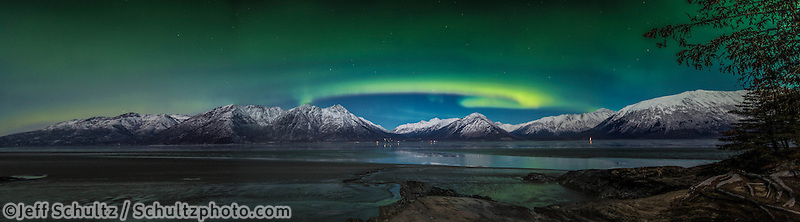 winter landscape shows Northern Lights (Aurora Borealis) in sky above moonlight on the Chugach Mountains that jut above Indian area and Turnagain Arm taken from Hope   Seward Highway January 2014