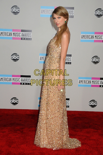 Taylor Swift.2011 American Music Awards - Arrivals held at Nokia Theatre LA Live, Los Angeles, California, USA..November 20th, 2011.ama amas ama's full length dress maxi  gold beige embellished jewel encrusted bead beaded dress ponytail side.CAP/ADM/BP.©Byron Purvis/AdMedia/Capital Pictures.
