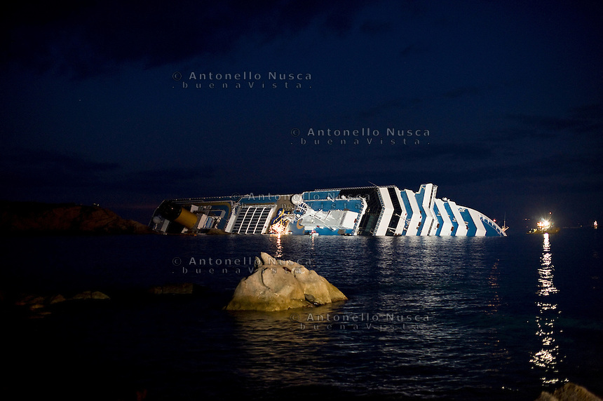 La nave da crociera Costa Concordia ancora arenata davanti al porto dell'Isola del Giglio..The stricken cruise liner Costa Concordia lies partially submerged off the Isola del Giglio..