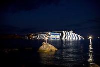 La nave da crociera Costa Concordia ancora arenata davanti al porto dell'Isola del Giglio..The stricken cruise liner Costa Concordia lies partially submerged off the Isola del Giglio..