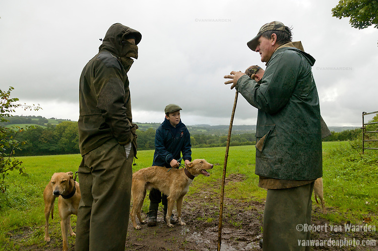 Male famers and a boy talk about the fox hunt while the hounds wait to be released in Wales, the United Kingdom.