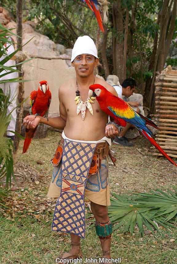 Man holding a pair of scarlet macaws or guacamayas at the recreation of an ancient Mayan market, Sacred Mayan Journey 2011 event, Riviera Maya, Quintana Roo, Mexico