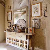 An old wooden sidetable with drawers has been adapted to store wine and placed beneath a mirror against a stone wall in the kitchen