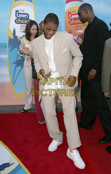 USHER.The 2004 Teen Choice Awards held at The Universal Ampitheatre in Universal City, California .August 8, 2004.full length, beige, cream suit, stripes, pointing,  gesture, white trainers, orange socks, funny.www.capitalpictures.com.sales@capitalpictures.com.Supplied By Capital Pictures