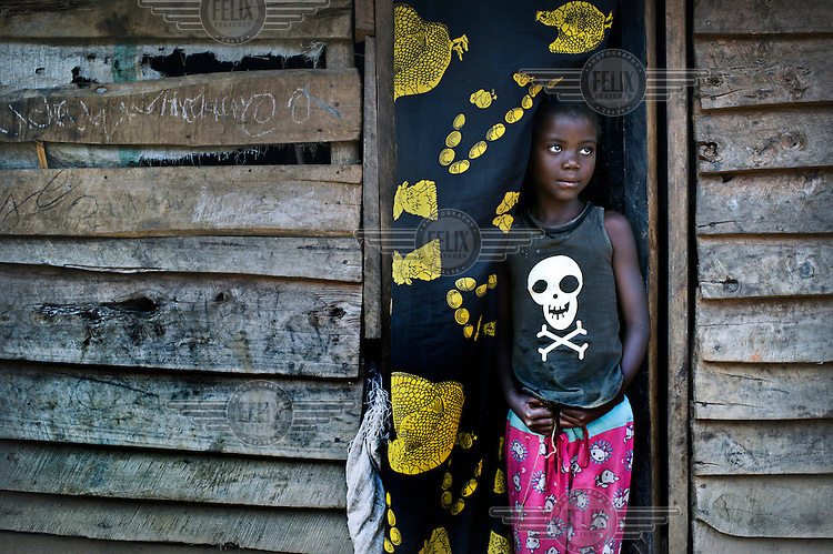 A child looks out from a house in the town of Shabunda which has been heavily hot my militia attacks. Displaced families are now living within host communities and share the already over-stretched or hardly existing public facilities for health, water, food and safety. The Congolese Army is poorly paid and ill disciplined resulting in high insecurity in the area due to the roaming militias.