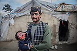 8 December 2013, Hemandi Market, Kabul Province, Afghanistan:  Oraghan (27) and his baby Pashtuna stand outside their shelter in the refugee camp at Helmandi Market on the outskirts of Kabul, Afghanistan. They are refugees from Uruzgan Province where Australian forces are winding up their long Afghan deployment before Christmas.  The family along many others  fled the area where retribution for those that helped coalition forces may be meted out after the withdrawal. Conditions in the camp are harsh and with winter snows approaching many are ill and short of food and medicines.    Picture by Graham Crouch