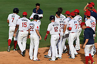 Teammates of Santiago Espinal (2) of the Greenville Drive pull off his jersey after he hit a walk-off single for a 2-1 win in a game against the Rome Braves on Sunday, August 13, 2017, at Fluor Field at the West End in Greenville, South Carolina. Greenville won, 2-1. (Tom Priddy/Four Seam Images)