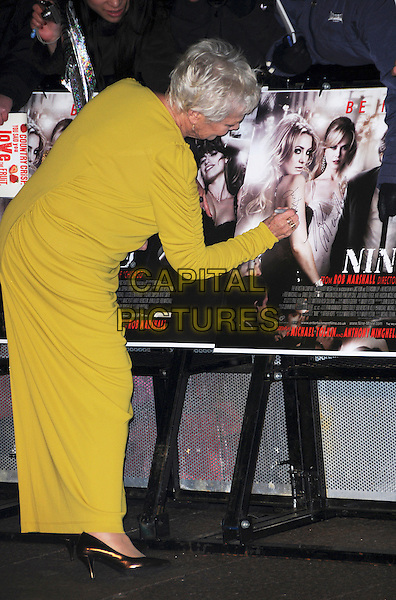 DAME JUDI DENCH .Attending the World Premiere of the film 'NINE' held at the Odeon cinema Leicester Square, London, England, UK,  3rd December 2009..full length long maxi dress sleeved sleeves gold back rear behind signing autograph green yellow chartreuse shiny shoes ruched.CAP/CAS.©Bob Cass/Capital Pictures.