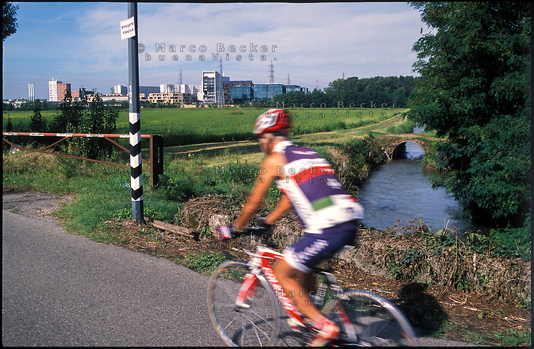 Assago (Milano), un ciclista sulla pista ciclabile lungo il Naviglio Pavese e i campi del Parco Agricolo Sud --- Assago (Milan), a cyclist on the bicycle path along the Naviglio Pavese canal and the fields in the Rural Park South
