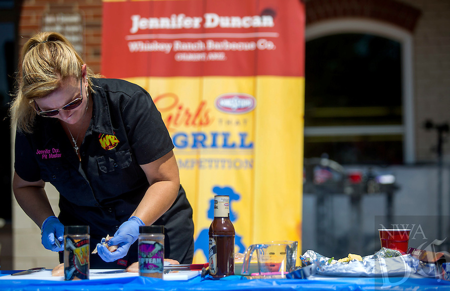 NWA Democrat-Gazette/JASON IVESTER<br /> Jennifer Duncan of Gilbert, Ariz., prepares food on Friday, May 6, 2016, during the Girls That Grill Competition on the downtown square as part of the Bentonville Film Festival.