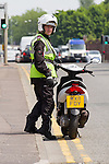© Joel Goodman - 07973 332324 . 19 June 2013 . A635 Ashton Old Road , Openshaw , UK . A traffic warden parks his motorbike on a double yellow line in order to issue a ticket to a vehicle parked on the pavement on Ashton Old Road today (Wednesday 19th June) . Photo credit : Joel Goodman