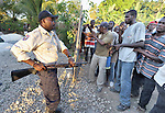 A distribution of food, tents and other emergency supplies dissolved into chaos when a group of men from a neighboring village invaded a January 30 distribution organized by the Lutheran World Federation, a member of the ACT Alliance, in the village of Gressier outside of Port-au-Prince, Haiti. Here a Haitian police officer holds the crowd back at gunpoint. A police woman eventually fired two shots into the air, motivating the crowd to flee. A January 12 earthquake ravaged the Caribbean nation, leaving hundreds of thousands hungry and increasingly frustrated and desperate.