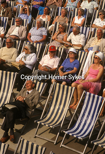 Seniors asleep in deck chairs enjoying summer holiday sun. Eastbourne England