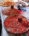A vendor table displays piles of two different types of hot chili peppers alongside small tomatos.  In the main market of Bitung, North Sulawesi, Indonesia.